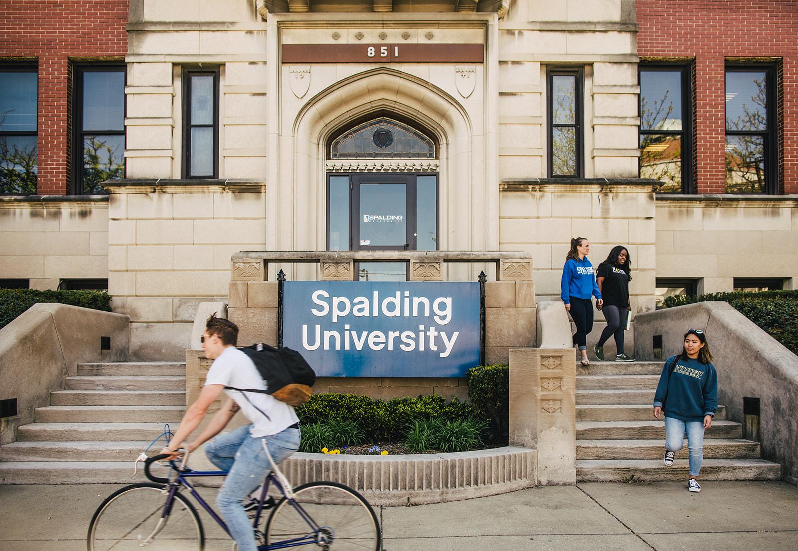 Student rides bike past Spalding Mansion complex entrance